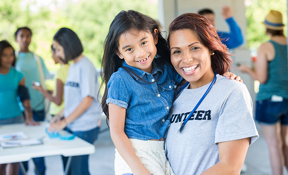 Female volunteer holding a young girl during a volunteer event; both are smiling at the camera