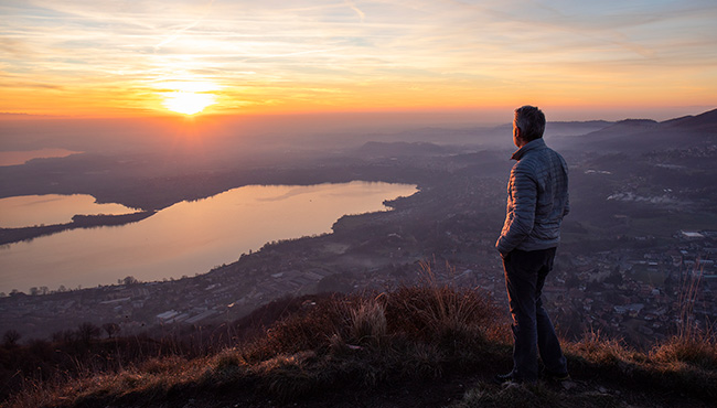 Hiker looking at the sun set over the horizon