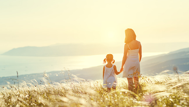 Mother and child daughter stand with their backs while looking at the ocean and sunset