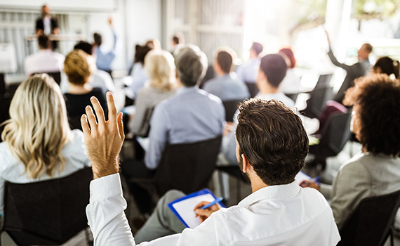 Back view of a businessman raising his hand at a seminar as he takes notes
