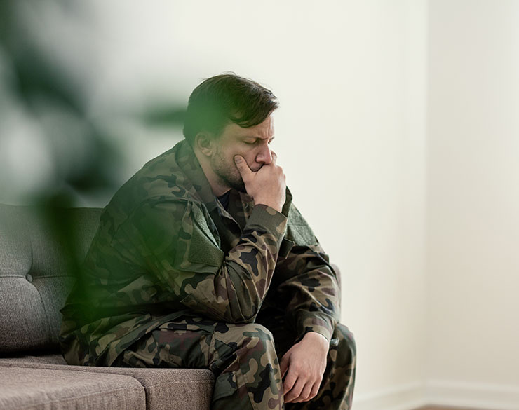 A male looking sad with his hand on his mouth, he is wearing an army uniform